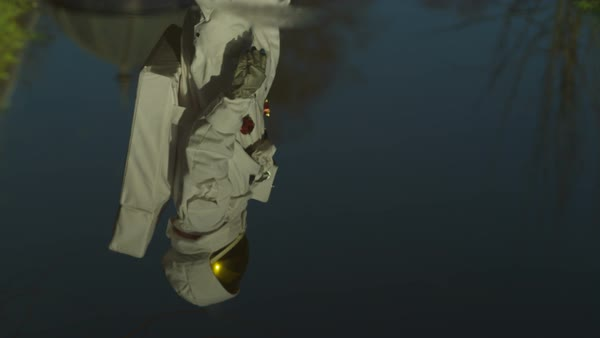Astronaut exploring earth & looking at his reflection in a puddle. Royalty-free stock video