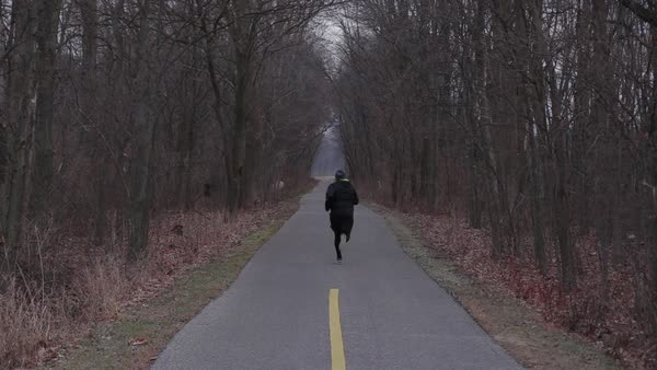 Hand-held shot of a man running on a road Royalty-free stock video