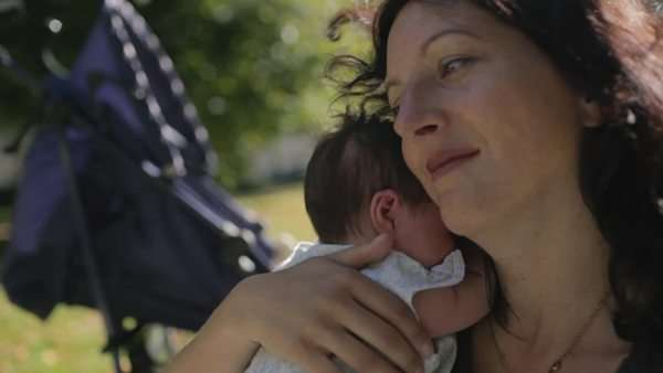 Medium close-up shot of a woman holding her baby in a park Royalty-free stock video