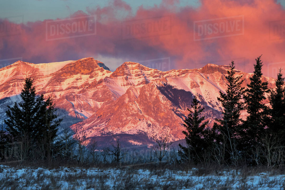 Brilliant colourful morning sunlight glow on a snow covered mountain ...