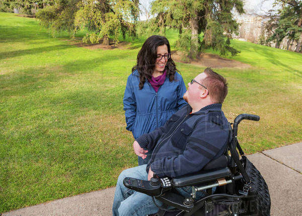 Disabled husband talking with his wife while walking in a park in autumn; Edmonton, Alberta, Canada Royalty-free stock photo