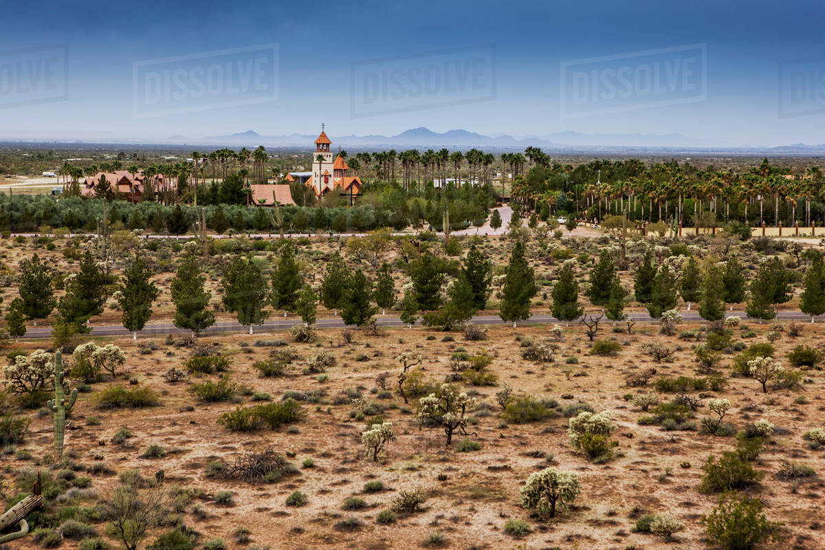Church steeple with cross and trees and plants on arid landscape