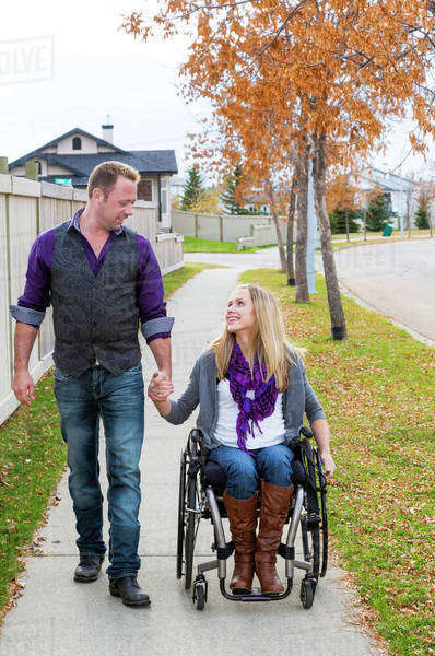 Husband and wife with disability spending time together outdoors; Spruce Grove, Alberta, Canada Royalty-free stock photo