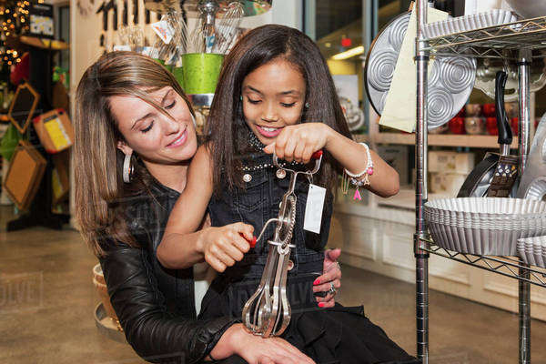 Young mother and her daughter shopping at a kitchen store looking at an egg beater; St. Albert, Alberta, Canada Royalty-free stock photo