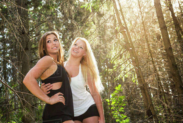 Two girlfriends posing together in the woods in the sunshine; Edmonton, Alberta, Canada Royalty-free stock photo