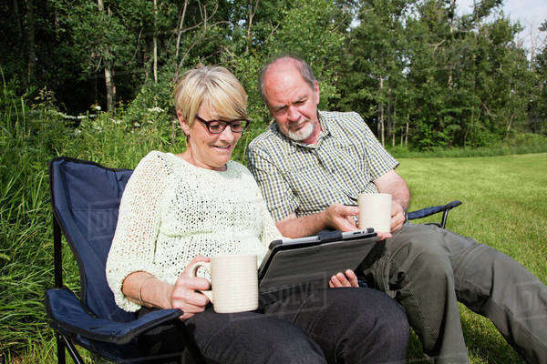 A senior couple sitting together in lawn chairs at a park looking at a tablet; Stony Plain, Alberta, Canada Royalty-free stock photo