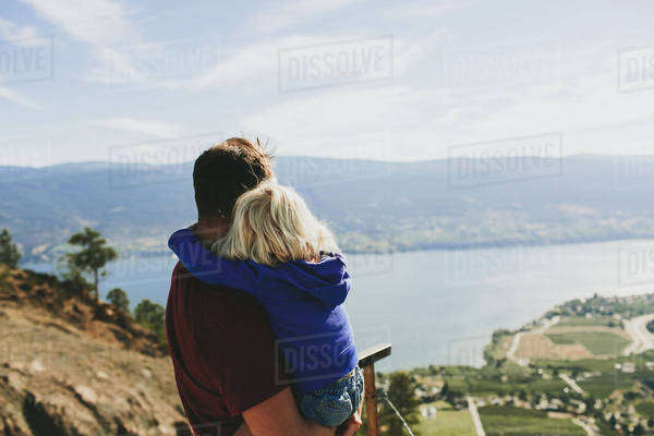 A father holds his young daughter as they look out over Lake Okanagan; Peachland, British Columbia, Canada Royalty-free stock photo