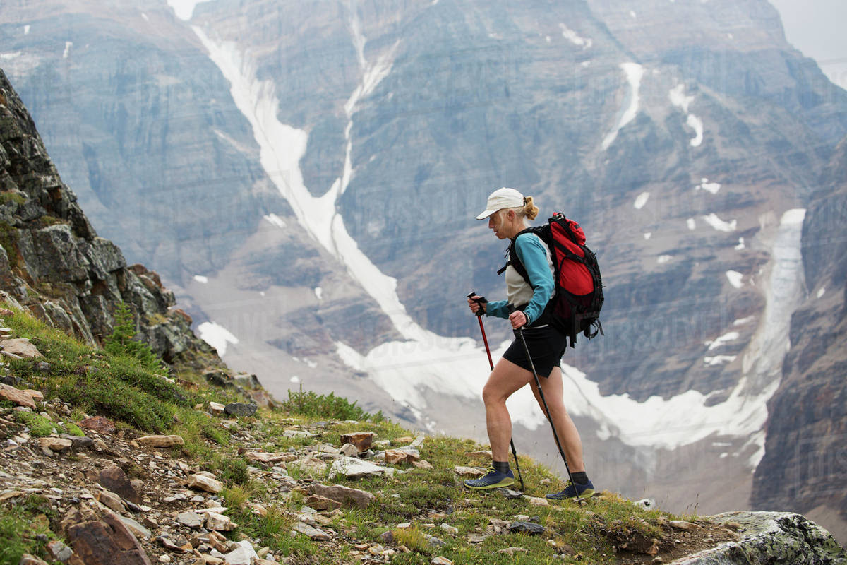 Female hiker with poles hiking up mountain path with ...