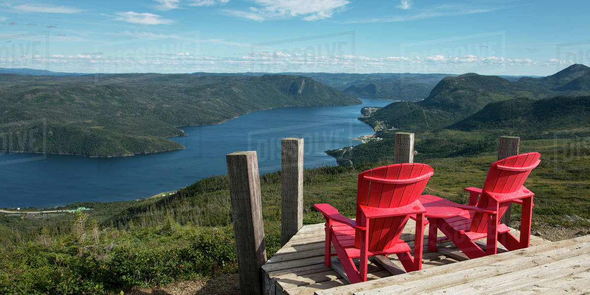 Two Red Adirondack Chairs On A Wooden Deck Overlooking Bonne Bay;  Newfoundland And Labrador, Canada
