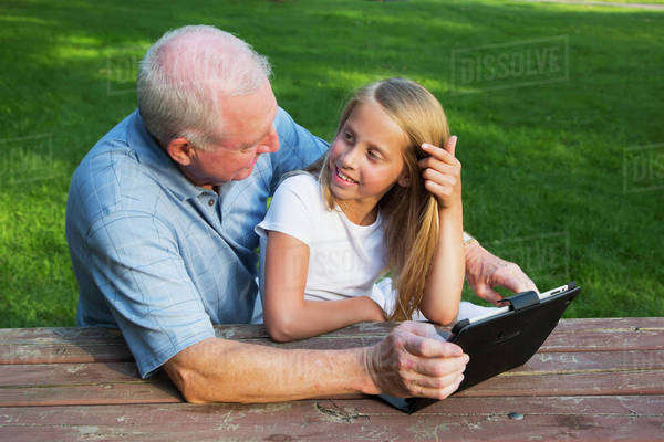 Grandfather and granddaughter checking their mobile devices together; Edmonton, Alberta, Canada Royalty-free stock photo