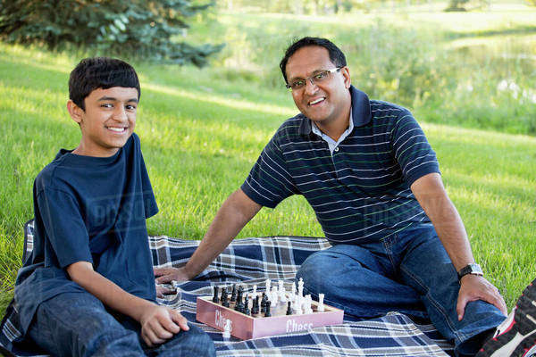 Father and son playing chess in a park; Edmonton, Alberta, Canada Royalty-free stock photo