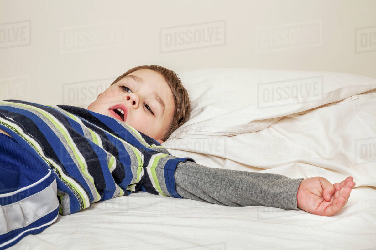 Young boy laying on a bed; Connecticut, United States of ...