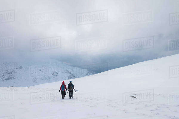 Two people walking in snow covered, winter conditions on Beinn an Dothaidh, near Bridge of Orchy; Argyll and Bute, Scotland Royalty-free stock photo