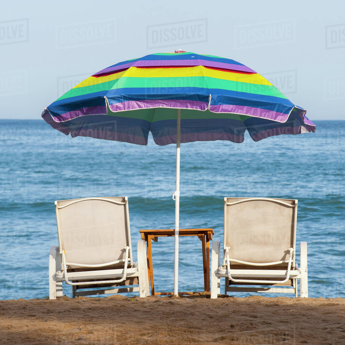 90c0814bee11 A Rainbow Beach Umbrella Over Two Lounge Chairs On The Beach At The Water's  Edge; Sayulita, Mexico