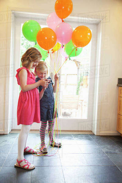 Two young girls standing inside a house with balloons while looking at pictures on a camera;Pacifica california united states of america Royalty-free stock photo
