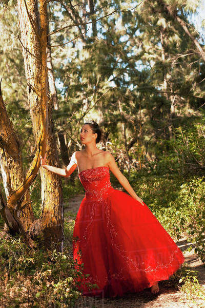 A woman in a formal red gown posing by a tree; Honolulu, Hawaii, United States of America Royalty-free stock photo