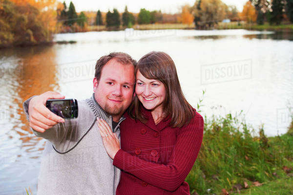 Young Married Couple Taking A Picture Of Themselves In A Park In Autumn; Edmonton, Alberta, Canada Royalty-free stock photo