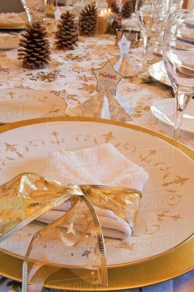 Close Up Of A Classy Christmas Table Setting With Gold Ribbon Around A Cloth Napkin On A Gold Rimmed Plate And Pine Cones In The Background; Calgary, Alberta, Canada Royalty-free stock photo