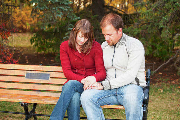 Young Married Couple Praying Together On A Park Bench; Edmonton, Alberta, Canada Royalty-free stock photo