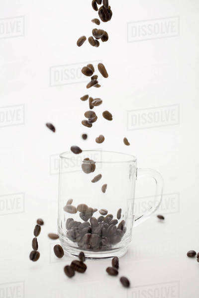 Coffee Beans Falling Into Clear Coffe Cup Royalty-free stock photo