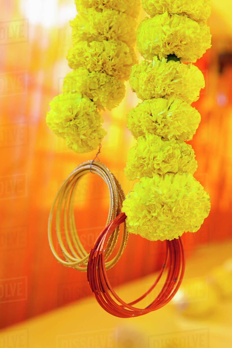 Strings Of Yellow Flowers With Gold And Red Bracelets Dangling From
