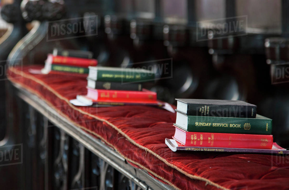 Piles Of Hymn And Service Books On A Bench In A Church