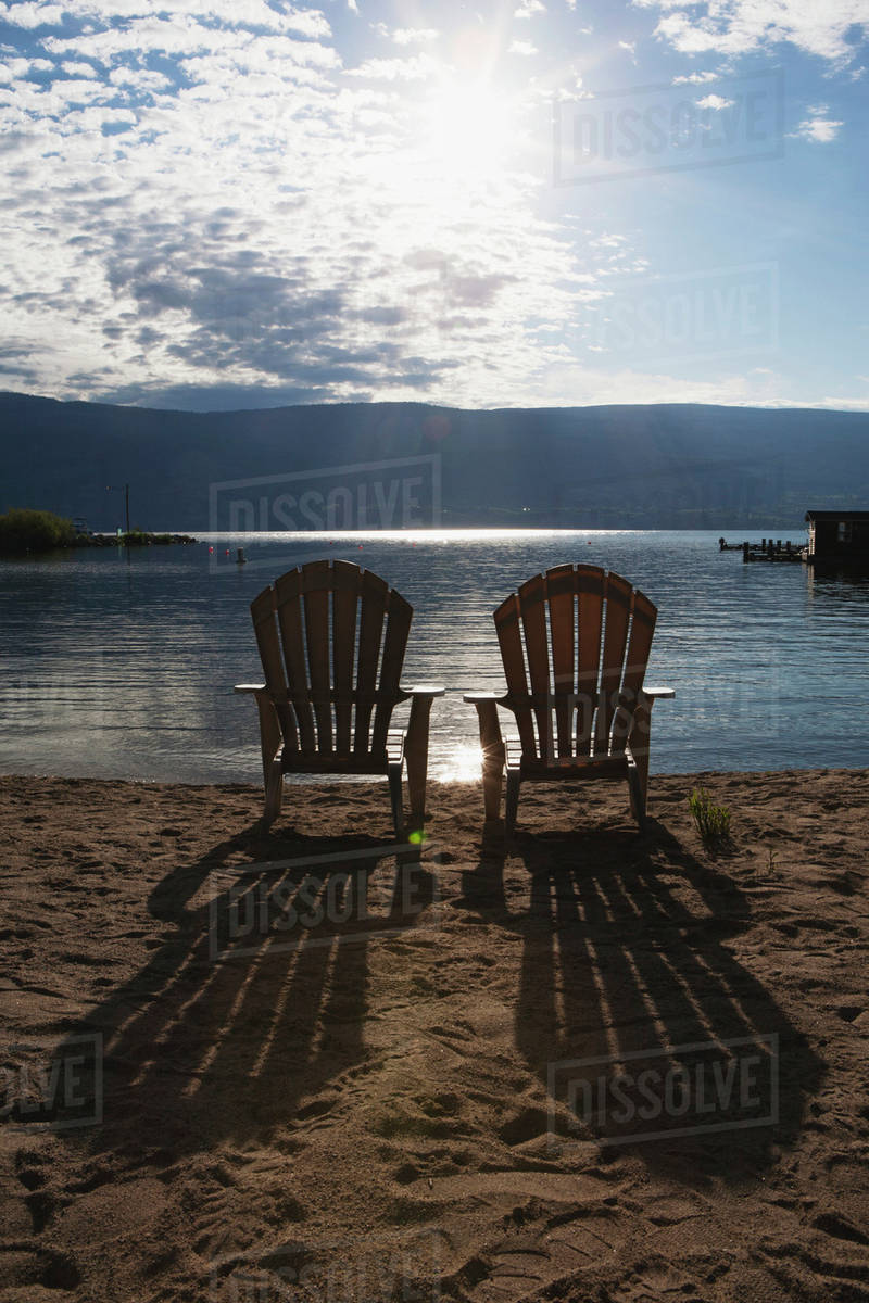 Two beach chairs on a beach with the sun burst out of the clouds and long shadows of the chairs on the sand;Summerland british columbia canada & Two beach chairs on a beach with the sun burst out of the clouds and ...
