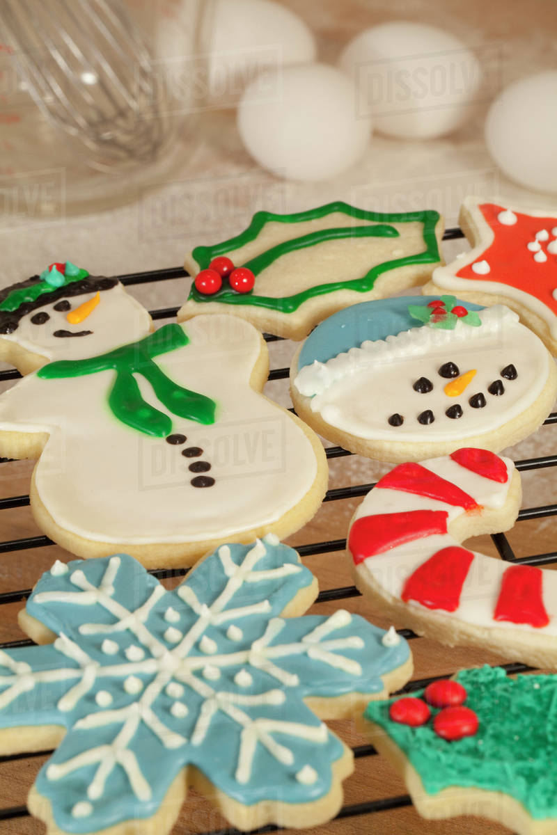 Closeup Of A Variety Of Homemade Christmas Sugar Cookies Decorated With Colorful Icing And Arranged On A Black Cooling Rack With Eggs And Measuring