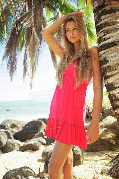 7776f1482c46c A young woman in a red dress poses by a palm tree on anini beach ...