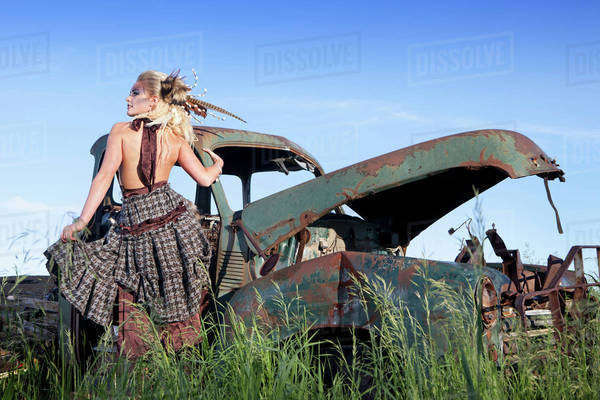 A Young Woman With Dramatic Makeup And Hairstyle By An Abandoned Vintage Car; Nisku, Alberta, Canada Royalty-free stock photo