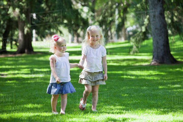 Two Sisters Walking Together In A Park; Edmonton, Alberta, Canada Royalty-free stock photo