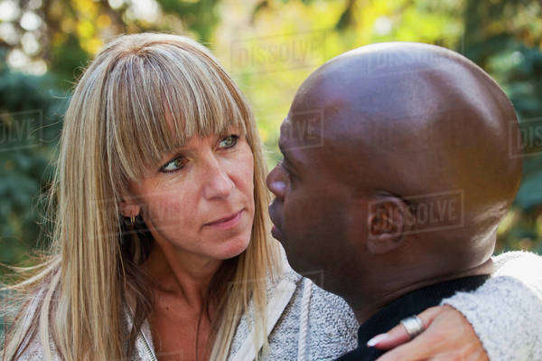 Interracial Married Couple Having A Deep Conversation In A Park; Edmonton, Alberta, Canada Royalty-free stock photo