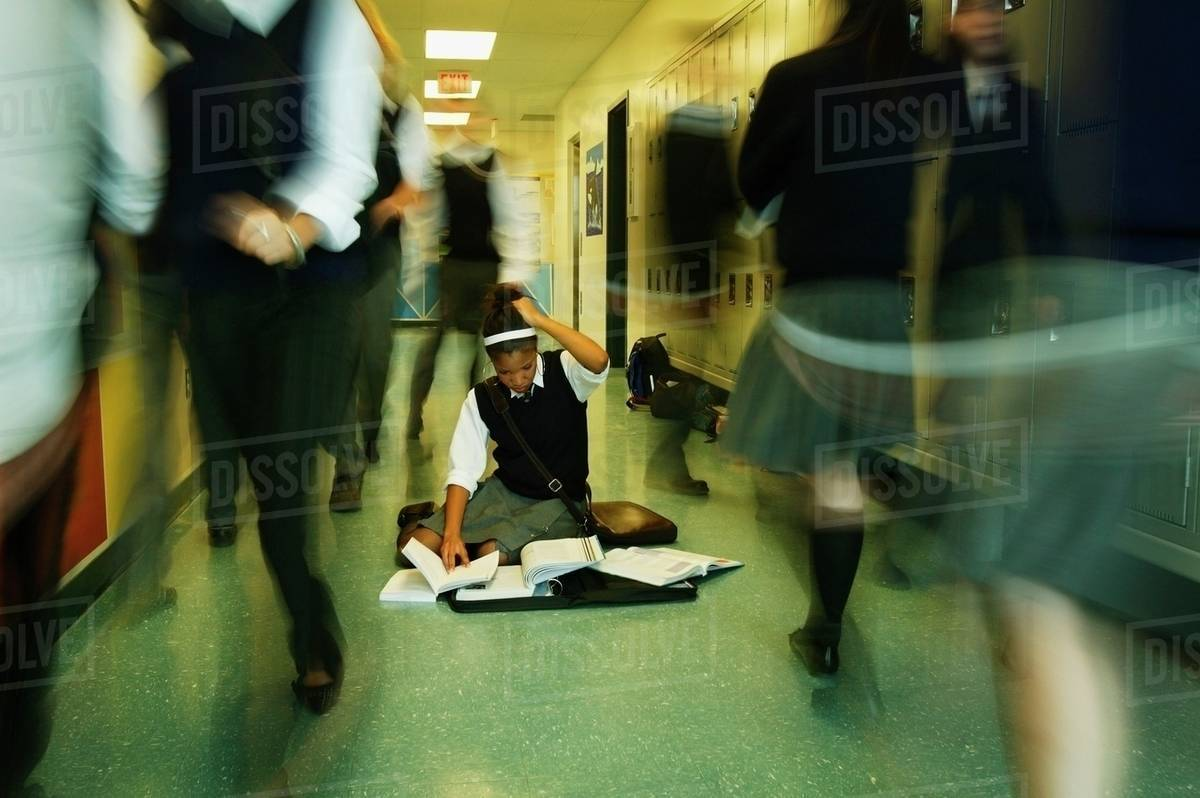 Girl In Crowded School Hallway With Books On The Floor Stock