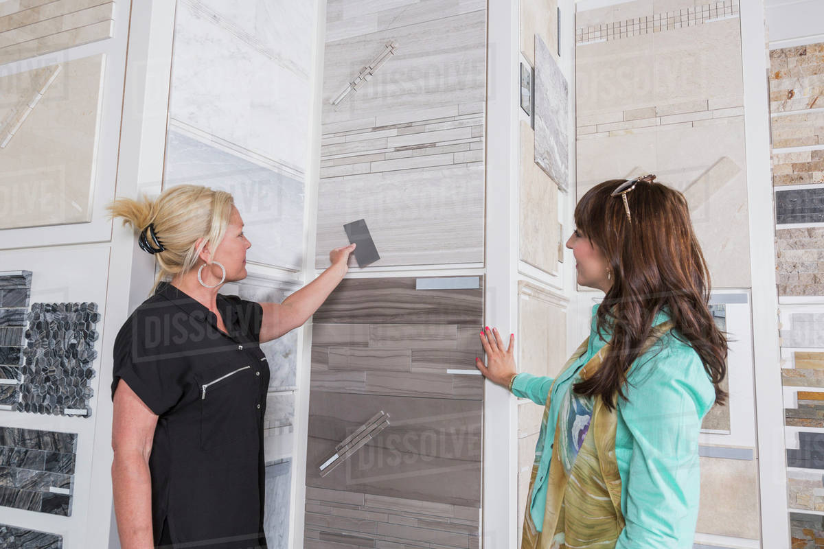 Design consultant and interior designer selecting tiles in showroom ...