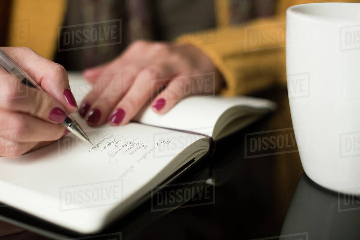 woman writing thoughts in a journal; toronto, ontario, canada