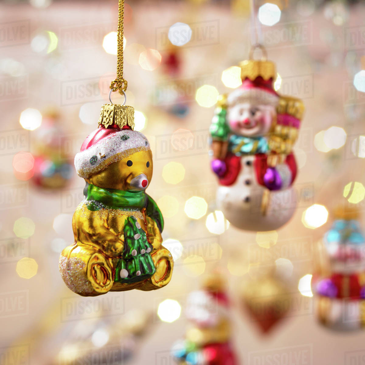 Hanging yellow teddy bear Christmas ornament with out of focus ornaments in the background; Victoria, British Columbia, Canada