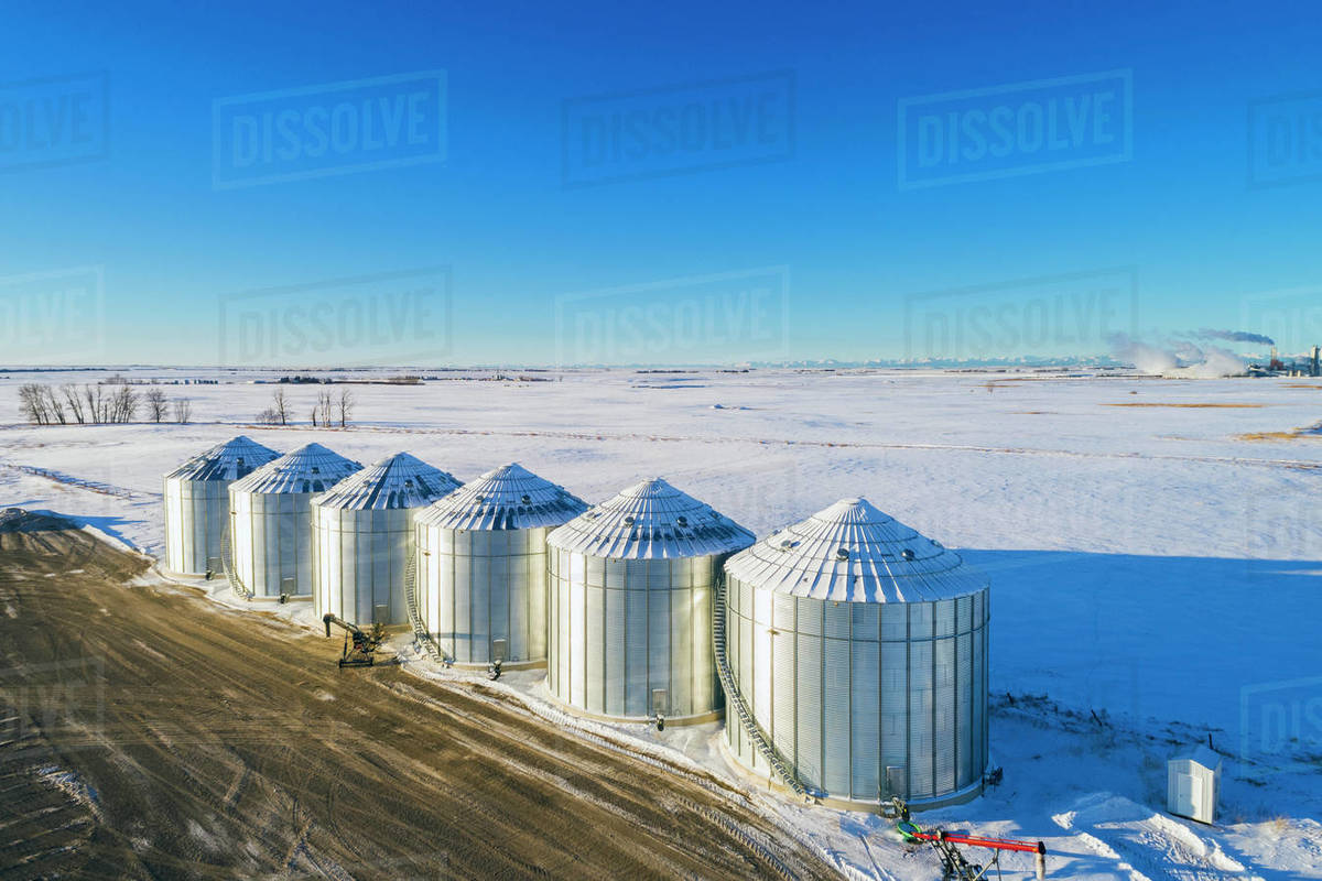 Aerial view of snow-covered large metal grain storage bins in a  snow-covered field with blue sky, South of Calgary