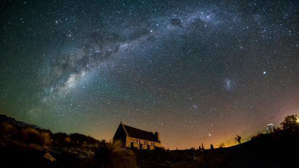 Mesmerizing scene of Aurora Australis (Southern Light) dancing behind Church of The Good Shepherd in Lake Tekapo, South Island with Magellanic Clouds and Milky Way rotating above. Timelapse  Royalty-free stock video