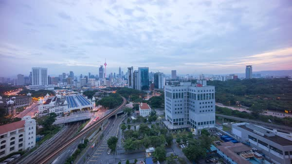Timelapse of a beautiful sunrise of Kuala Lumpur city view from rooftop of a building with moving vehicle, clouds and sunlight burst. Royalty-free stock video