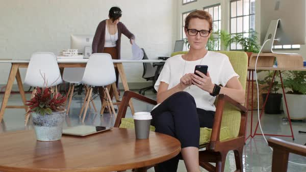 Daily office situation, business woman checks emails on mobile phone while having coffee Royalty-free stock video