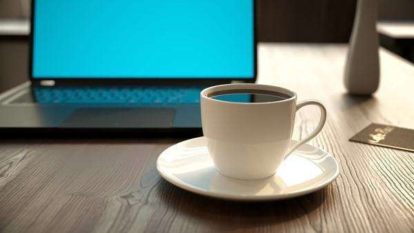 Laptop and a cup of coffee on a table in office or cafeteria Royalty-free stock video