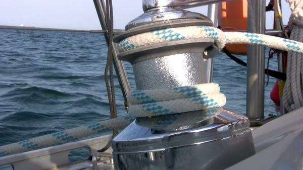 Men rotates the yacht winch and pull the halyard against the backdrop of blue sea and blue sky. Winch sparkles in the sun Royalty-free stock video