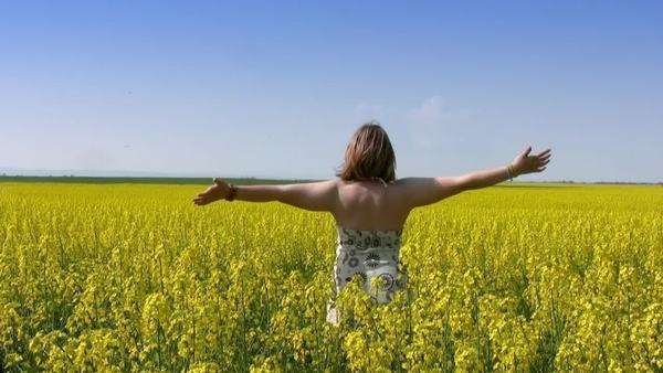 Czech republic bright yellow flowers of oilseed rape in spring vast teen girl closed her eyes and spins with his arms raised in a field of canola mightylinksfo