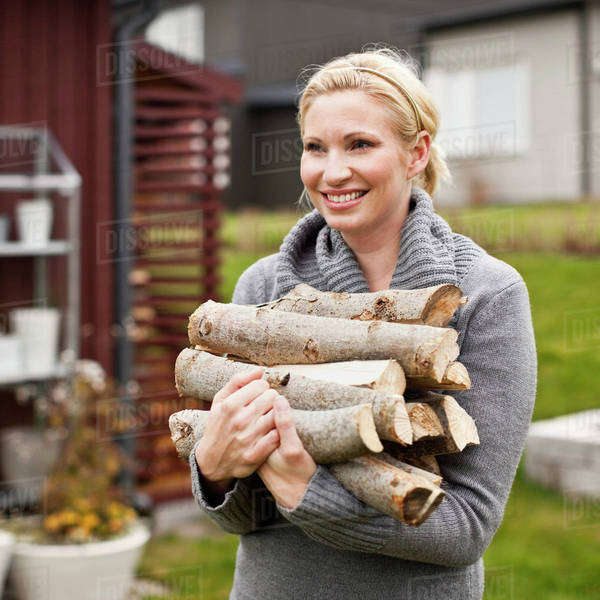 Happy mid adult woman carrying firewood in back yard Royalty-free stock photo