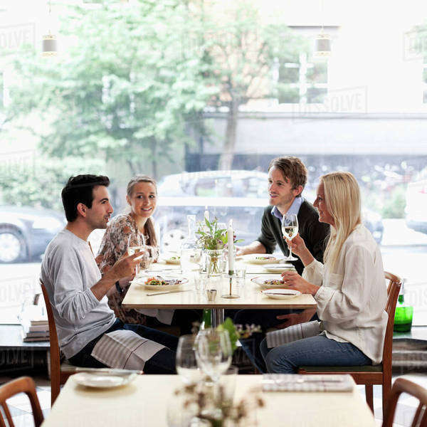 Group of friends communicating at restaurant table Royalty-free stock photo