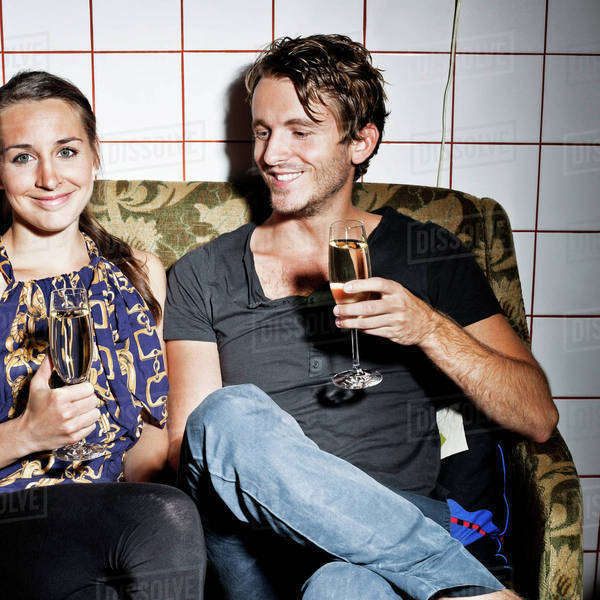 Couple holding champagne flutes on sofa at saloon Royalty-free stock photo