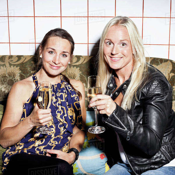 Portrait of happy female friends holding champagne flutes on sofa Royalty-free stock photo