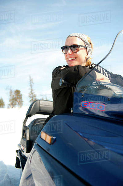 Happy young woman sitting on snow mobile Royalty-free stock photo