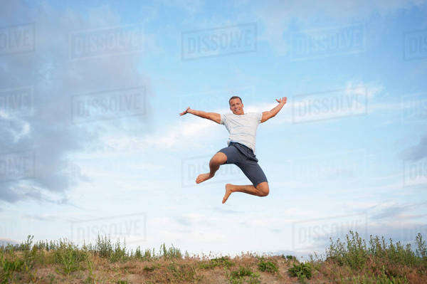Excited young man jumping in mid-air against cloudy sky Royalty-free stock photo