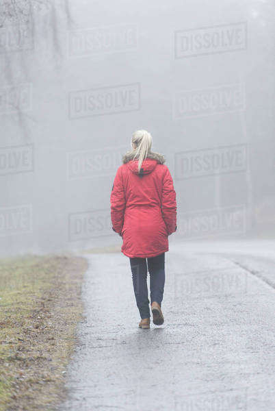 Rear view of young woman walking on road in a foggy day Royalty-free stock photo